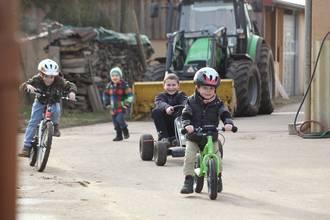 Kinder fahren Fahrrad und Kettcar