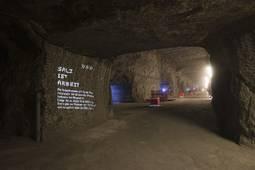 Leuchtschriften unter Tage weisen den Besuchern den Weg
