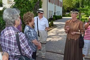 Eine Gruppe bei einer Führung vor dem Schloss Lehen